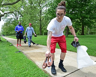 YOUNGSTOWN, OHIO - MAY 19, 2018: Jacob Tocco of Youngstown places a pair of shoes that belonged to someone that passed away from a opioid drug overdose near the sidewalk inside Wick Park, Saturday afternoon. DAVID DERMER | THE VINDICATOR