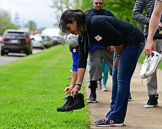 YOUNGSTOWN, OHIO - MAY 19, 2018: Elena Andino of Youngstown places a pair of shoes that belonged to someone that passed away from a opioid drug overdose near the sidewalk inside Wick Park, Saturday afternoon. DAVID DERMER | THE VINDICATOR
