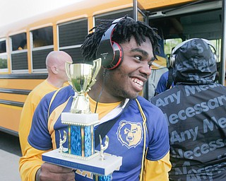 William D. Lewis the Vindicator   East HS 10th grade rugby player Elija smith carries the trophy as the team returns to the school 5-20-18 after beating Shaker Hgts to win the state championship.