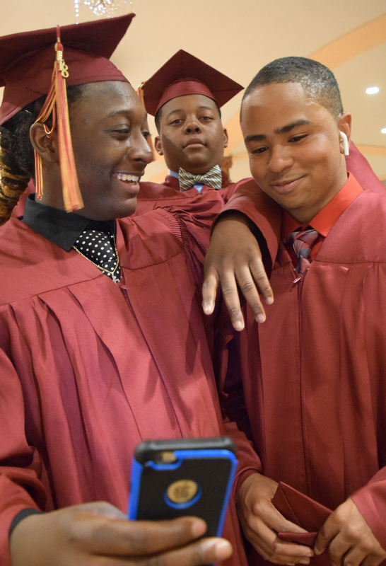 William D. Lewis The Vindicator Mooney grads from left, Antonio Riley, Kris Winford and Willie Young talke a selfie before 5-27-18 commencement at Stambaugh Auditorium.