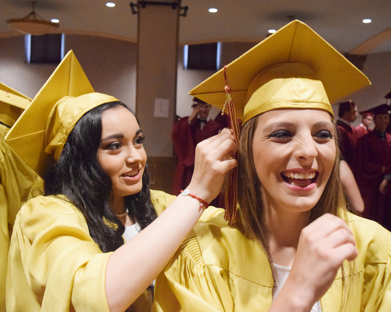 William D. Lewis The Vindicator Mooney grad Olivia Saunders(right) gets some help with her cap from fellow grad Angelina Toss before 5-27-18 commencement at Stambaugh.