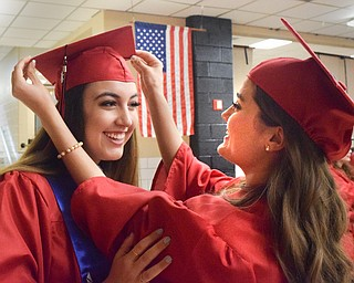 William D. Lewis The Vindicator  Canfield grad Madeline Remby, left, gets help with her motarboard from Sarah Veverka before 6-1-18 commencement at CHS.