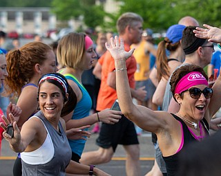 Scott R. Galvin | The Vindicator.Melody Ward and Jen Mihok of Boardman wave to spectators at the start of the race for the first inaugural Youngstown Marathon on Sunday, June 3, 2018.