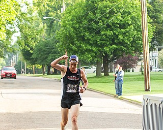 Scott R. Galvin   The Vindicator.Mack Mettille of Canfield celebrates as he crosses the finish line first in the 5K run at the first inaugural Youngstown Marathon on Sunday, June 3, 2018.