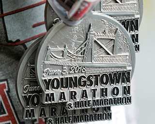 Scott R. Galvin   The Vindicator.A worker with the Youngstown Marathon holds medals for participants of the marathon and half-marathon run on Sunday, June 3, 2018.