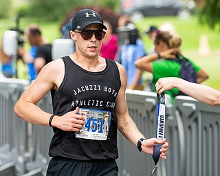 Scott R. Galvin   The Vindicator.Jon Hutnyan of Baltimore, Maryland, receives his medal for crossing the finish line first in the half marathon run during the first inaugural Youngstown Marathon on Sunday, June 3, 2018.