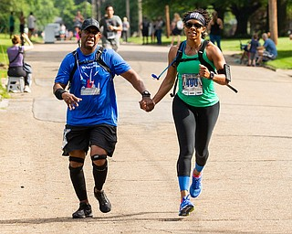 Scott R. Galvin | The Vindicator.Dwayne Dickens of Maryland holds hands with Misty Lawson of Virginia as they cross the finish line of the half marathon together during the first inaugural Youngstown Marathon on Sunday, June 3, 2018.