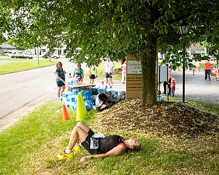 Scott R. Galvin | The Vindicator.Linda Reeder of Westerville, Ohio, rests under the shade of a tree following her finish in the half marathon at the first inaugural Youngstown Marathon on Sunday, June 3, 2018.