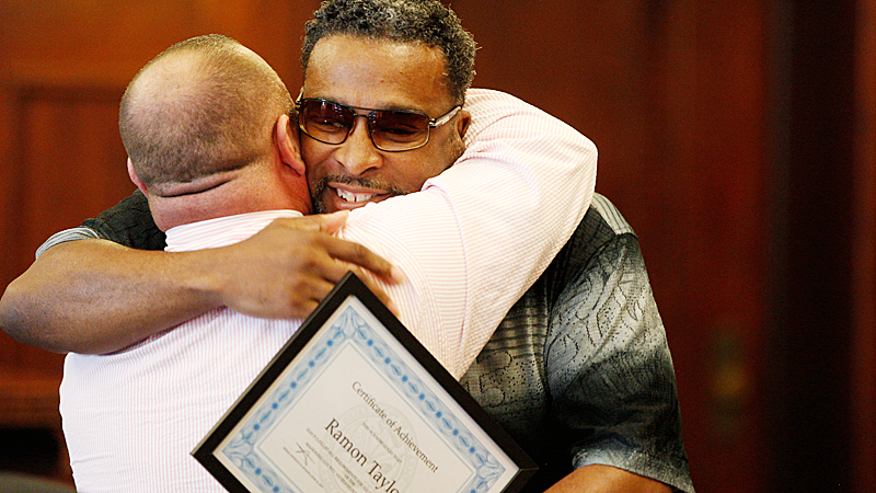 Ramon Taylor, right, hugs his mentor, Chris Derr, at the Honor Court graduation in Mahoning County Common Pleas Court on Tuesday. Taylor completed the program and had a pending criminal case against him dismissed as a result.