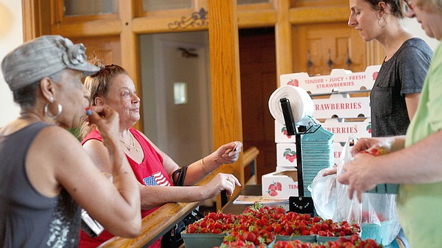Delores Franklin, front left, and Debbie Maderitz buy strawberries from Janelle McHugh, back right, and Barb Yoder of Huffman Fruit Farm during the Youngstown Farmers Market at the B&O Station in downtown Youngstown on Wednesday.
