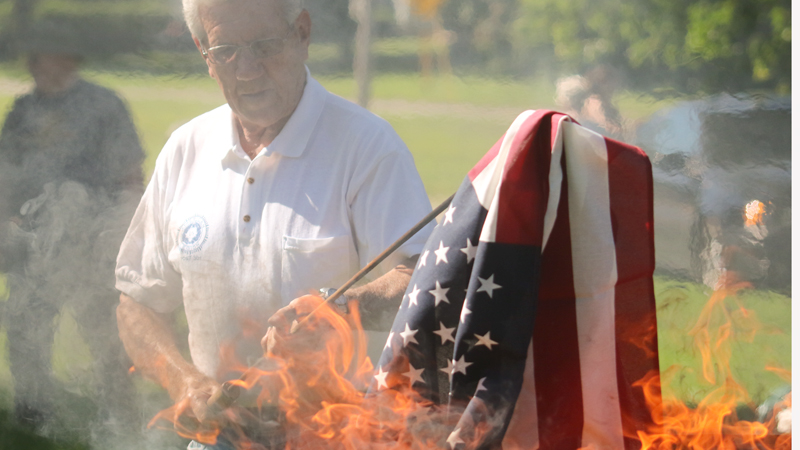 Bob Kirchner of American Legion Post 301 holds a flag in the flames during Austintown's flag-burning ceremony Thursday in the Veterans' Memorial Park.