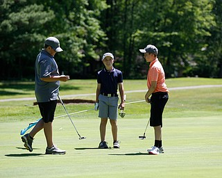 From left to right, Nate Kelly, Anthony Cesario, and Nate Smrek talk after putting during the Greatest Golfer junior qualifier on Thursday at Trumbull Country Club in Warren.