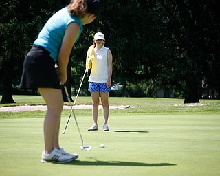 Hannah Ogden, left, puts while Megan Stuneburner watches during the Greatest Golfer junior qualifier on Thursday at Trumbull Country Club in Warren.