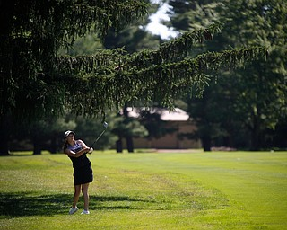Jackie Adler hits her ball from under the trees during the Greatest Golfer junior qualifier on Thursday at Trumbull Country Club in Warren.