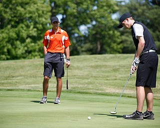 Cameron Colbert, right, puts his ball while Lance Chieffo watches during the Greatest Golfer junior qualifier on Thursday at Trumbull Country Club in Warren.