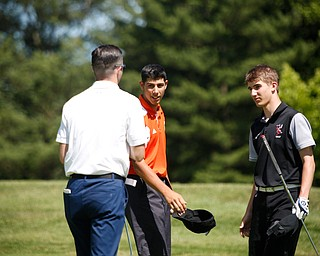 From left, Seamus Chrystal, Lance Chieffo, and Cameron Colbert talk after putting during the Greatest Golfer junior qualifier on Thursday at Trumbull Country Club in Warren.
