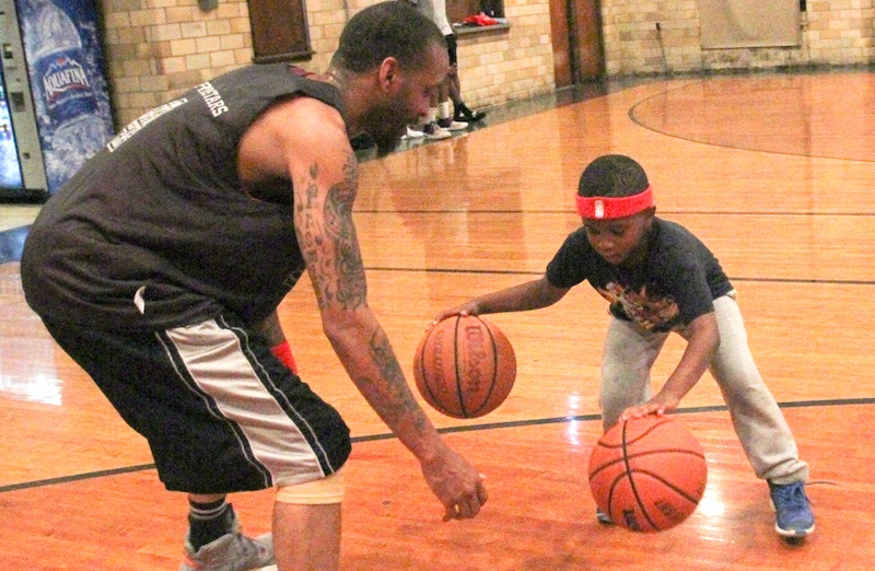 Kevin Thomas, who plays in a basketball league at the Calvin Center, shares a moment with his son, Lajuan, 6, before an adult game. Seventy teams play games at the Youngstown center.