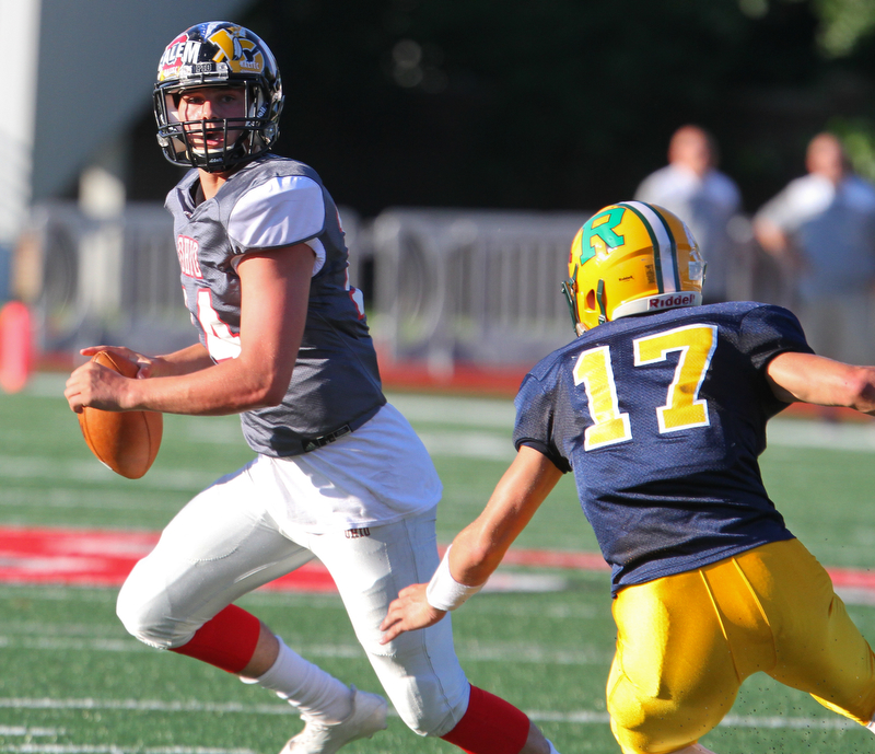 William D. Lewis The Vindicator Ohio QB Mitch Davidson(14) of Salem eludes Penn's Cj Gailey of Blackhawk during 6-28-18 Penn Ohio game in Salem.