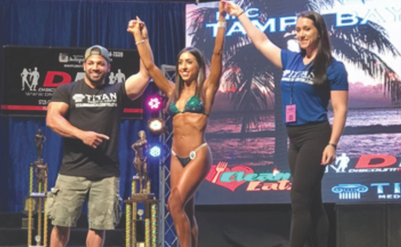 Girard native Katie O'Neill, center, won four bodybuilding titles on June 2 in Florida. Holding her hands are Ron Galup and Heather Eslinger of Titan Medical, the competition sponsor.