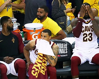 Cleveland Cavaliers forward LeBron James (23) sits on the bench with center Tristan Thompson, left, and guard George Hill during the second half of Game 2 of basketball's NBA Finals against the Golden State Warriors in Oakland, Calif., Sunday, June 3, 2018. The Warriors won 122-103. (AP Photo/Ben Margot)