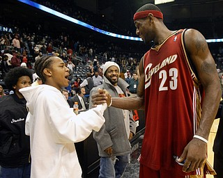 Rapper Bow Wow, left, is greeted by Cleveland Cavaliers' LeBron James as music producer Jermaine Dupri looks on in the background  after the Cavs defeated the Atlanta Hawks Tuesday, Nov. 9, 2004 in Atlanta. (AP Photo/John Bazemore)