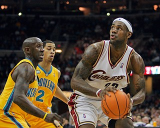 Cleveland Cavaliers' LeBron James, right, coils to shoot against New Orleans Hornets' Bobby Jackson and Jannero Pargo (2) in the fourth quarter of an NBA basketball game Tuesday, Feb. 27, 2007, in Cleveland. James' 35 point sled the Cavaliers to a 97-89 win over New Orleans. (AP Photo/Mark Duncan)
