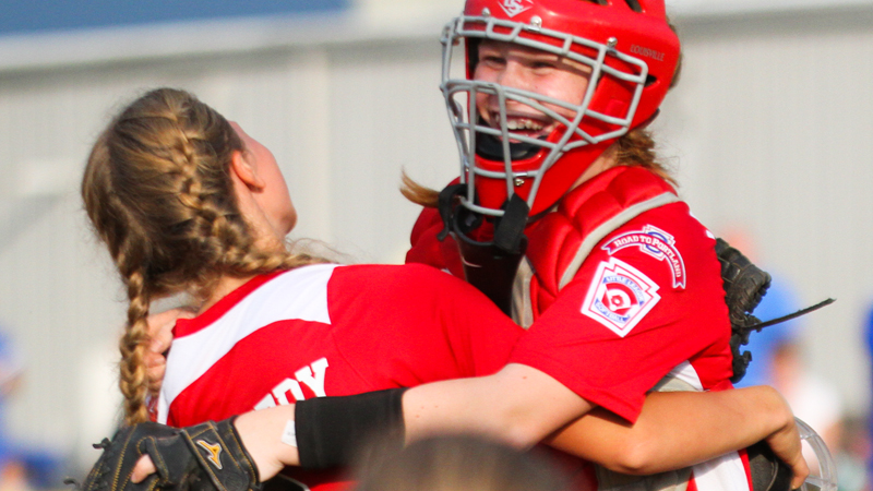 Canfield 12U softball players celebrate after defeating Poland at Fields Of Dreams in Boardman on Monday.