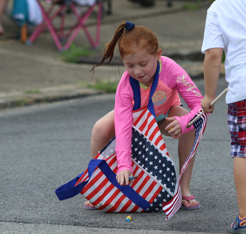 Brynn Cappelli (7) of Boardman grabs candy during the Struthers Fourth of July Parade on Wednesday afternoon.  Dustin Livesay  |  The Vindicator  7/4/18  Struthers