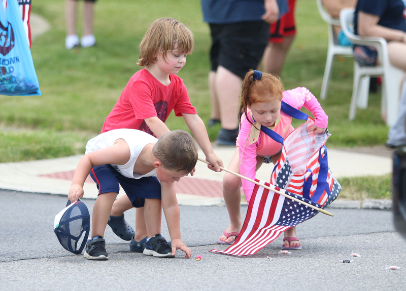 Cousins, Colin Hallquist of Struthers, Dylan Anderson (4) of Chicago, and Bryn Cappelli (7) of Boardman pick up candy during the Struthers Fourth of July Parade on Wednesday afternoon.  Dustin Livesay  |  The Vindicator  7/4/18  Struthers