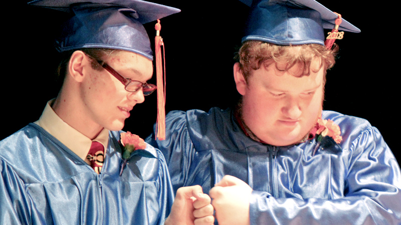 Potential Development High School graduates Gregory Burkett, left, and Edwin Gurney bump fists during Monday afternoon's commencement at Stambaugh Auditorium in Youngstown.