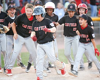 Canfield celebrates as Dylan Mancini runs into home after hitting a home run during the Little League baseball 11-U playoff game against Boardman on Wednesday.