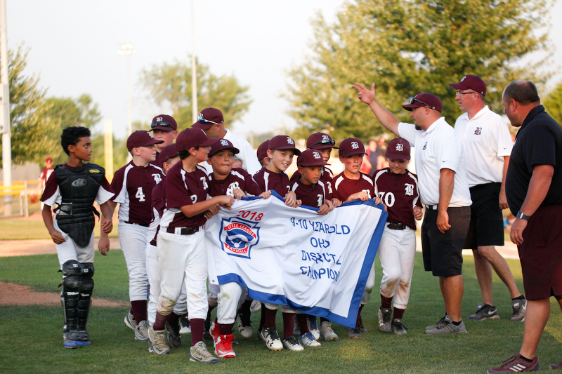 Boardman's 10u team holds their banner after winning the district championship game against Poland 13-10.