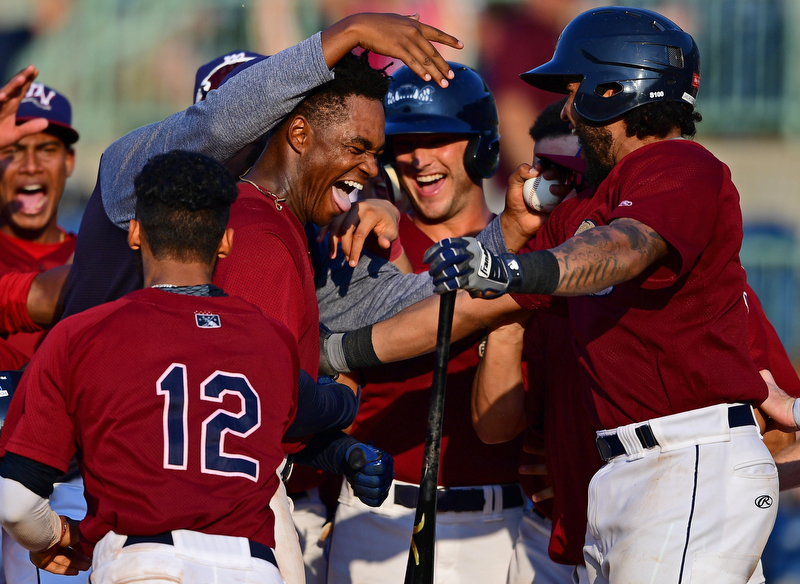 NILES, OHIO - JULY 15, 2018: Mahoning Valley Scrappers' Hosea Nelson is mobbed by his teammates at home plate after hitting a a walk-off home run off Hudson Valley Renegades relief pitcher Jesus Ortiz in the ninth inning, Sunday, July 15, 2018, in Niles. The Scrappers won 8-6. DAVID DERMER | THE VINDICATOR
