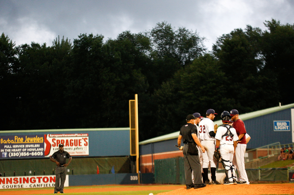 The Scrappers infield huddle on the mound as storm clouds roll in during the fourth inning of Tuesday night's game.