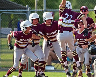 NORTH CANTON, OHIO - JULY 26, 2018: New Albany's Ben Liebel jumps onto home plate before being mobbed by his teammates after hitting a solo home run off Boardman starting pitcher Gavin Hyde in the fourth inning of a Little League baseball game, Thursday night in North Canton. New Albany won 3-1. DAVID DERMER | THE VINDICATOR