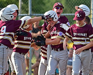 NORTH CANTON, OHIO - JULY 26, 2018: New Albany's Ben Liebel is mobbed by his teammates after hitting a solo home run off Boardman starting pitcher Gavin Hyde in the fourth inning of a Little League baseball game, Thursday night in North Canton. New Albany won 3-1. DAVID DERMER | THE VINDICATOR