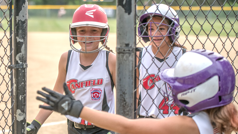 Canfield's Sam Economous, left, and Riley Billak, center, are all smiles returning to the dugout after scoring and are congratulated by teammate Brooke Opalick during 10-U state tournament action in Tallmadge on Monday. Canfield won 18-4 against Austintown.