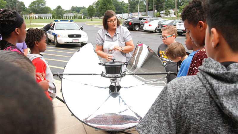Jennifer Gasser of Hubbard, one of the Solar Sisters, explains how a parabolic solar cooker works to Paul C. Bunn Elementary School summer school students in Youngstown.