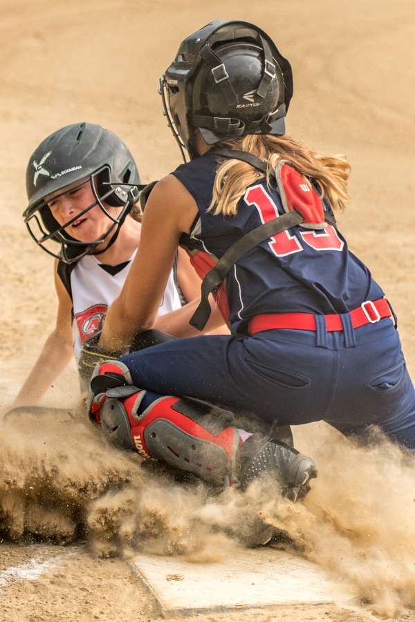 DIANNA OATRIDGE | THE VINDICATOR Austintown's Kylie Folkwein tags out Canfield's Marina Koenig as she slides into home during 10U tournament action in Tallmadge on Monday. Canfield won 18-4 to advance to the championship.