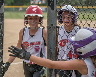 DIANNA OATRIDGE | THE VINDICATOR Canfield's Sam Economous (left) and Riley Billak (center) are all smiles returning to the dugout after scoring and are congratulated by teammate Brooke Opalick (right) during 10U state tournament action in Tallmadge on Monday. Canfield won 18-4 against Austintown.