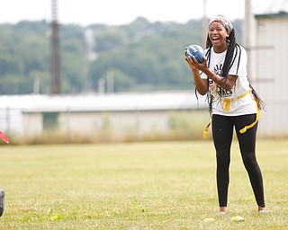 Donavan Gillison, 16, of Youngstown, laughs as she catches a football at the Grrridiron Girls Flag Football Camp at Glacier Field in Struthers on Tuesday. EMILY MATTHEWS | THE VINDICATOR
