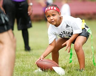Aliyah Giles, 6, of Boardman, participates in a drill on how to handle a football at the Grrridiron Girls Flag Football Camp at Glacier Field in Struthers on Tuesday. EMILY MATTHEWS | THE VINDICATOR