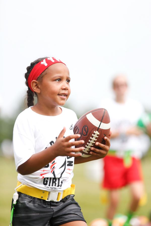 Aliyah Giles, 6, of Boardman, practices techniques for holding a football while running at the Grrridiron Girls Flag Football Camp at Glacier Field in Struthers on Tuesday. EMILY MATTHEWS | THE VINDICATOR