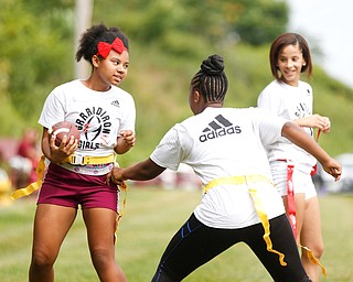 Janay Shaw, 15, center, of Youngstown, grabs the flag of Laionia Williams, 13, left, of Youngstown, while Karisha Agosto, 15, right, of Youngstown, watches at the Grrridiron Girls Flag Football Camp at Glacier Field in Struthers on Tuesday. EMILY MATTHEWS | THE VINDICATOR