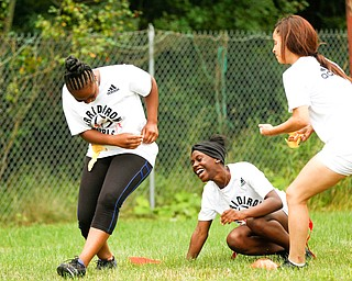 Iazia Wyan, 15, center, of Youngstown laughs after Janay Shaw, 15, left, of Youngstown, loses one of her flags to  Karisha Agosto, 15, right, of Youngstown, at the Grrridiron Girls Flag Football Camp at Glacier Field in Struthers on Tuesday. EMILY MATTHEWS | THE VINDICATOR