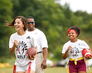 Karisha Agosto, 15, left, and Laionia Williams, 13, right, both of Youngstown, practice running with a football at the Grrridiron Girls Flag Football Camp at Glacier Field in Struthers on Tuesday. EMILY MATTHEWS | THE VINDICATOR