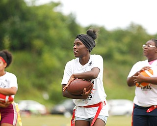 Iazia Wyan, 15, center, Laionia Williams, 13, left, and Calya Findley 15, all of Youngstown, practice running with a football at the Grrridiron Girls Flag Football Camp at Glacier Field in Struthers on Tuesday. EMILY MATTHEWS | THE VINDICATOR