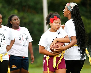 Donavan Gillison, 16, right, of Youngstown, hands the ball off to Laionia Williams, 13, of Youngstown, while Janay Shaw, 15, far left, and Calya Findley, 15, both of Youngstown, watch and wait for their turn at the Grrridiron Girls Flag Football Camp at Glacier Field in Struthers on Tuesday. EMILY MATTHEWS | THE VINDICATOR