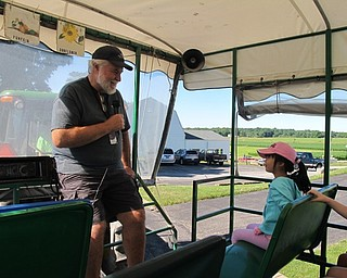 Neighbors | Jessica Harker.Instructor Bill gave information during the tractor tour of the MetroParks farms during the Food Quest camp.
