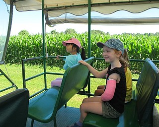 Neighbors | Jessica Harker.Amy Zhana (front) along with Riley Pieren (back) listen as the insturctor explained different animal and plant facts during a tractor tour of the MetroParks farms on July 9.